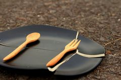 Spoon and fork on a crack  black plate. Royalty Free Stock Images