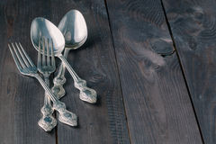 Spoon and fork on dark wooden table Stock Images