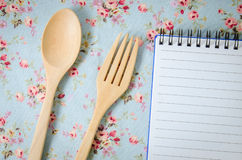 Spoon, fork and empty paper on vintage style tablecloth Royalty Free Stock Photos