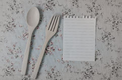Spoon, fork and empty paper on vintage style tablecloth Stock Photography