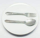 Spoon and fork. Isolated spoon and fork in dish Stock Photos