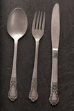 Spoon, fork and knife on black background Royalty Free Stock Photo
