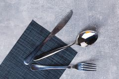 Spoon, fork and knife on a kitchen serving napkin. Royalty Free Stock Image