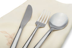 Spoon, fork and a knife lie on serviette Royalty Free Stock Image