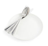 Spoon, fork and knife over the white plate Royalty Free Stock Photos