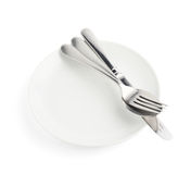 Spoon, fork and knife over the white plate Stock Image