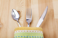 Spoon,fork,knife with tablecloth. On woody table Stock Images