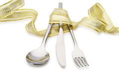 Spoon, fork and a knife tied up celebratory ribbon. It is isolated on a white background stock photo