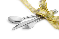 Spoon, fork and a knife tied up celebratory ribbon. It is isolated on a white background stock image