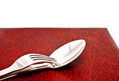 Spoon and fork on menu cover Royalty Free Stock Photos