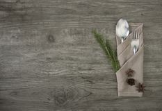 Spoon and fork with napkin setting on wood table top view royalty free stock photo
