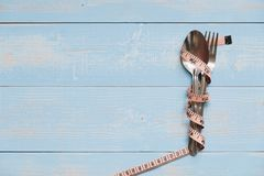 spoon and fork with pink Measuring tape on blue pastel color wooden table. stock photo