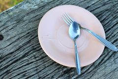 Spoon and fork on a pink plate Royalty Free Stock Photos