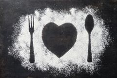 Spoon, Fork and plate in heart shape, flour sprinkled around the royalty free stock photo