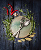 Spoon and Fork on plate with herbs and spices frame on dark blue wooden table Royalty Free Stock Images