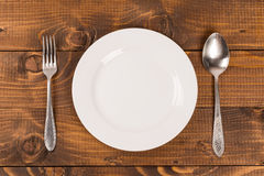 Spoon and fork on a plate Stock Photos