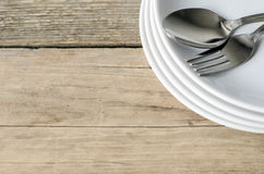 Spoon and fork on a plate Stock Images
