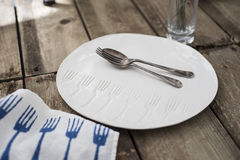Spoon and Fork on White Dinner Plate with Engraved Fork Pattern Royalty Free Stock Image