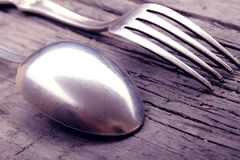 Spoon and fork on a worn wooden texture Royalty Free Stock Photography