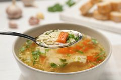 Spoon with fresh homemade chicken soup on blurred background. Closeup stock photos