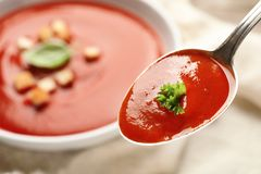 Spoon with fresh homemade tomato soup on blurred background, closeup. royalty free stock photos
