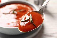 Spoon with fresh homemade tomato soup on blurred background. Closeup royalty free stock image