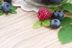 Spoon of fresh raspberries. Fresh raspberry anf blueberries with green leaves as frame  on wooden table Royalty Free Stock Photos