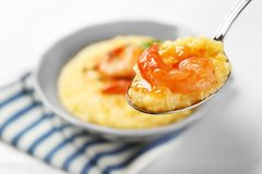 Spoon with fresh tasty shrimp and grits royalty free stock images