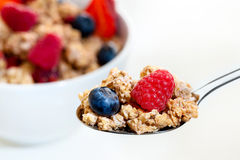 Spoon with fruit muesli and bowl in background. Royalty Free Stock Image