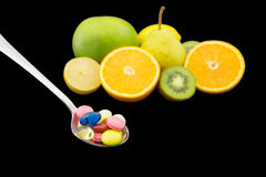 Spoon full of colorful pills. Against the background of fresh fruits Stock Images