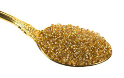 Spoon full of gold glass beads Stock Images