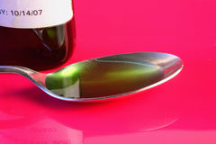 Spoon full of green cough syrup. Graphic close-up Stock Images