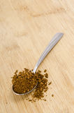 Spoon full of instant coffee on wood. A spoonful of instant coffe on a wooden background/foreground Stock Images