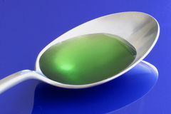 A spoon full of medicine 2422. A spoonful of green narcotic cough syrup. Blue backgound. Extreme close-up with spoon reflecting on table Stock Image