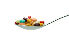 Spoon full of medicine pills. Spoon full of variety medicine pills isolated on white background Stock Photography