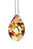 Spoon full of medicine pills. Spoon full of variety medicine pills isolated on white background Stock Photos