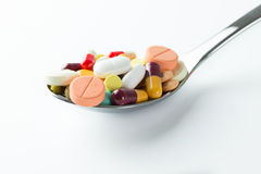 Spoon full of medicine pills Stock Images