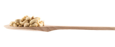 Spoon full of peanuts isolated. Wooden spoon full of peanuts isolated over white background, side view Stock Image