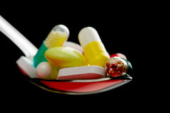 Spoon full of various pills Royalty Free Stock Photography