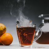 Spoon in glass cup with steaming. Black tea stock photo