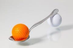 Spoon and golf balls Stock Photos