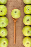 Spoon with green apple lying on the sackcloth among green apples Royalty Free Stock Photo
