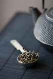 Spoon of green tea and teapot Stock Photo