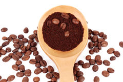 Spoon with ground coffee on beans Royalty Free Stock Image
