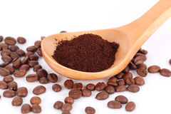 Spoon with ground coffee on beans Royalty Free Stock Photos