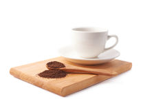 Spoon of ground coffee and cup on a plate Royalty Free Stock Photography