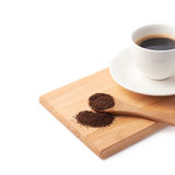 Spoon of ground coffee and cup on a plate Stock Photos