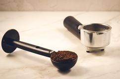 Spoon with ground coffee and holder/black spoon with ground coff royalty free stock images