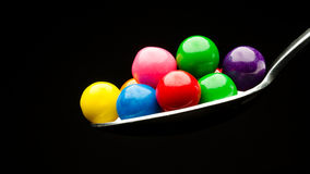 Spoon holding many gumballs Royalty Free Stock Photography