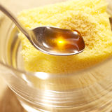 Spoon with honey beeing poured on cake Royalty Free Stock Image